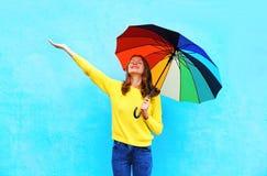 Mujer joven sonriente feliz que sostiene el paraguas colorido en el día del otoño que mira para arriba sobre fondo azul colorido Imágenes de archivo libres de regalías