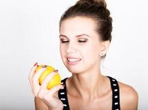 Mujer joven sonriente feliz que sostiene los limones jugosos frescos Consumición sana, frutas y verduras Fotos de archivo