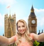 Mujer joven sonriente feliz que toma el selfie Imágenes de archivo libres de regalías