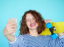 Mujer joven sonriente hermosa con el monopatín amarillo brillante Fotografía de archivo libre de regalías