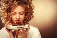 Mujer joven sonriente hermosa con una torta imagenes de archivo