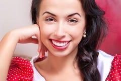 Mujer joven sonriente hermosa en alineada roja Imagenes de archivo