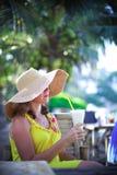 Mujer joven sonriente hermosa en las gafas de sol que llevan el sombrero con un cóctel en el café de la playa Imagen de archivo