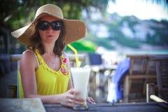 Mujer joven sonriente hermosa en las gafas de sol que llevan el sombrero con un cóctel en el café de la playa Foto de archivo