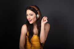 Mujer joven sonriente hermosa que escucha la música en radio él Fotografía de archivo