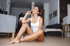 Mujer joven sonriente hermosa que habla en el teléfono que se sienta a piernas cruzadas en el piso en sala de estar Foto de archivo