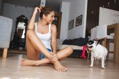 Mujer joven sonriente hermosa que se sienta a piernas cruzadas en el piso en la sala de estar que mira el dogo francés juguetón a Imagen de archivo