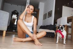Mujer joven sonriente hermosa que se sienta a piernas cruzadas en el piso en sala de estar con el dogo francés juguetón a un lado Foto de archivo libre de regalías