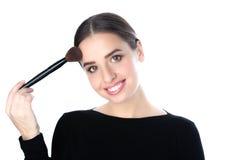 Mujer joven sonriente hermosa que sostiene un cepillo del polvo Fotografía de archivo libre de regalías