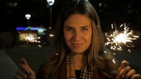 Mujer joven sonriente hermosa que sostiene una bengala Escena de la noche Muchacha sonriente joven que sostiene la bengala en su  Foto de archivo