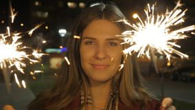 Mujer joven sonriente hermosa que sostiene una bengala Escena de la noche Muchacha sonriente joven que sostiene la bengala en su  Imagenes de archivo