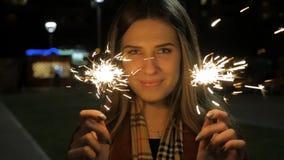 Mujer joven sonriente hermosa que sostiene una bengala Escena de la noche Muchacha sonriente joven que sostiene la bengala en su  Fotos de archivo libres de regalías