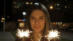 Mujer joven sonriente hermosa que sostiene una bengala Escena de la noche Muchacha sonriente joven que sostiene la bengala en su  Foto de archivo libre de regalías