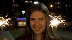 Mujer joven sonriente hermosa que sostiene una bengala Escena de la noche Muchacha sonriente joven que sostiene la bengala en su  Imágenes de archivo libres de regalías
