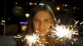 Mujer joven sonriente hermosa que sostiene una bengala Escena de la noche Muchacha sonriente joven que sostiene la bengala en su  Imagen de archivo