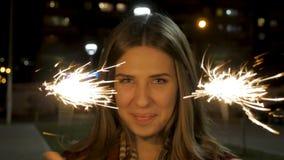 Mujer joven sonriente hermosa que sostiene una bengala Escena de la noche Muchacha sonriente joven que sostiene la bengala en su  Imagen de archivo libre de regalías