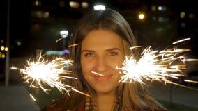 Mujer joven sonriente hermosa que sostiene una bengala Escena de la noche Muchacha sonriente joven que sostiene la bengala en su  Fotos de archivo
