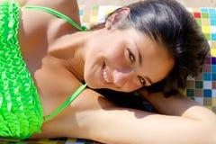 Mujer joven sonriente linda en bikini en el primer feliz del banco colorido fotografía de archivo