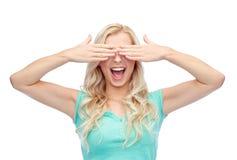 Mujer joven sonriente o muchacha adolescente que la cubre ojos Foto de archivo libre de regalías