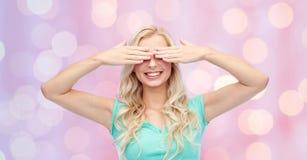 Mujer joven sonriente o muchacha adolescente que la cubre ojos Imágenes de archivo libres de regalías