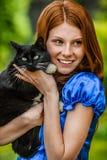 Mujer joven sonriente pelirroja con el gato negro Fotos de archivo libres de regalías