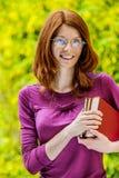 Mujer joven sonriente pelirroja con los libros Foto de archivo libre de regalías