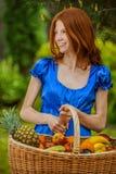 Mujer joven sonriente pelirroja con una cesta de fruta Foto de archivo libre de regalías