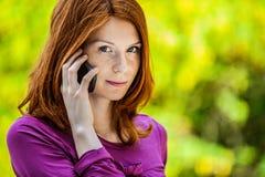 Mujer joven sonriente pelirroja que habla en el teléfono Imagen de archivo