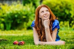 Mujer joven sonriente pelirroja que miente en hierba Imágenes de archivo libres de regalías