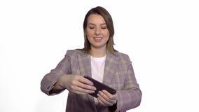 Mujer joven sonriente positiva que juega a juegos en el teléfono móvil aislado sobre el fondo blanco almacen de metraje de vídeo