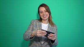 Mujer joven sonriente positiva que juega a juegos en el teléfono móvil aislado sobre fondo verde metrajes