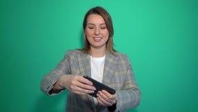 Mujer joven sonriente positiva que juega a juegos en el teléfono móvil aislado sobre fondo verde almacen de video