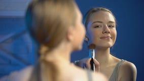 Mujer joven sonriente que aplica el polvo y la fabricaci?n de cara de gesto del beso en espejo almacen de video