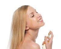 Mujer joven sonriente que aplica perfume Fotos de archivo