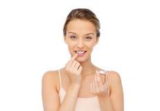 Mujer joven sonriente que aplica protector labial a sus labios Fotografía de archivo libre de regalías