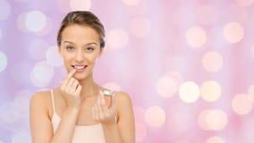 Mujer joven sonriente que aplica protector labial a sus labios Fotos de archivo libres de regalías