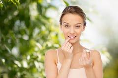 Mujer joven sonriente que aplica protector labial a sus labios Foto de archivo