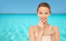Mujer joven sonriente que aplica protector labial a sus labios Foto de archivo libre de regalías