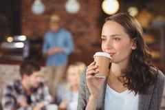 Mujer joven sonriente que bebe de la taza para llevar Imágenes de archivo libres de regalías