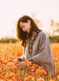 Mujer joven sonriente que camina en prado de las amapolas imágenes de archivo libres de regalías