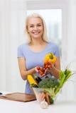 Mujer joven sonriente que cocina verduras en casa Fotos de archivo libres de regalías