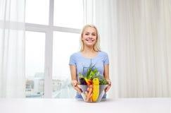 Mujer joven sonriente que cocina verduras en casa Imagen de archivo libre de regalías