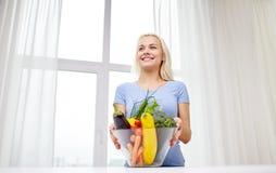 Mujer joven sonriente que cocina verduras en casa Imagenes de archivo