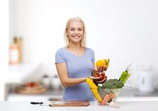 Mujer joven sonriente que cocina verduras en cocina Foto de archivo