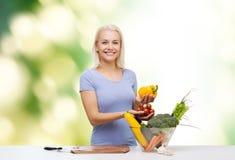 Mujer joven sonriente que cocina verduras sobre verde Imagen de archivo libre de regalías