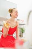 Mujer joven sonriente que come el plátano en cocina Foto de archivo