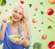 Mujer joven sonriente que come la ensalada vegetal verde Imagen de archivo