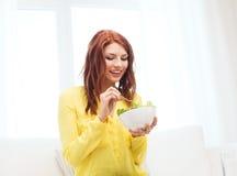 Mujer joven sonriente que come la ensalada verde en casa Fotografía de archivo libre de regalías