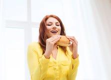 Mujer joven sonriente que come la hamburguesa en casa Fotos de archivo libres de regalías