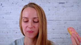 Mujer joven sonriente que come un buñuelo y que bebe el café metrajes